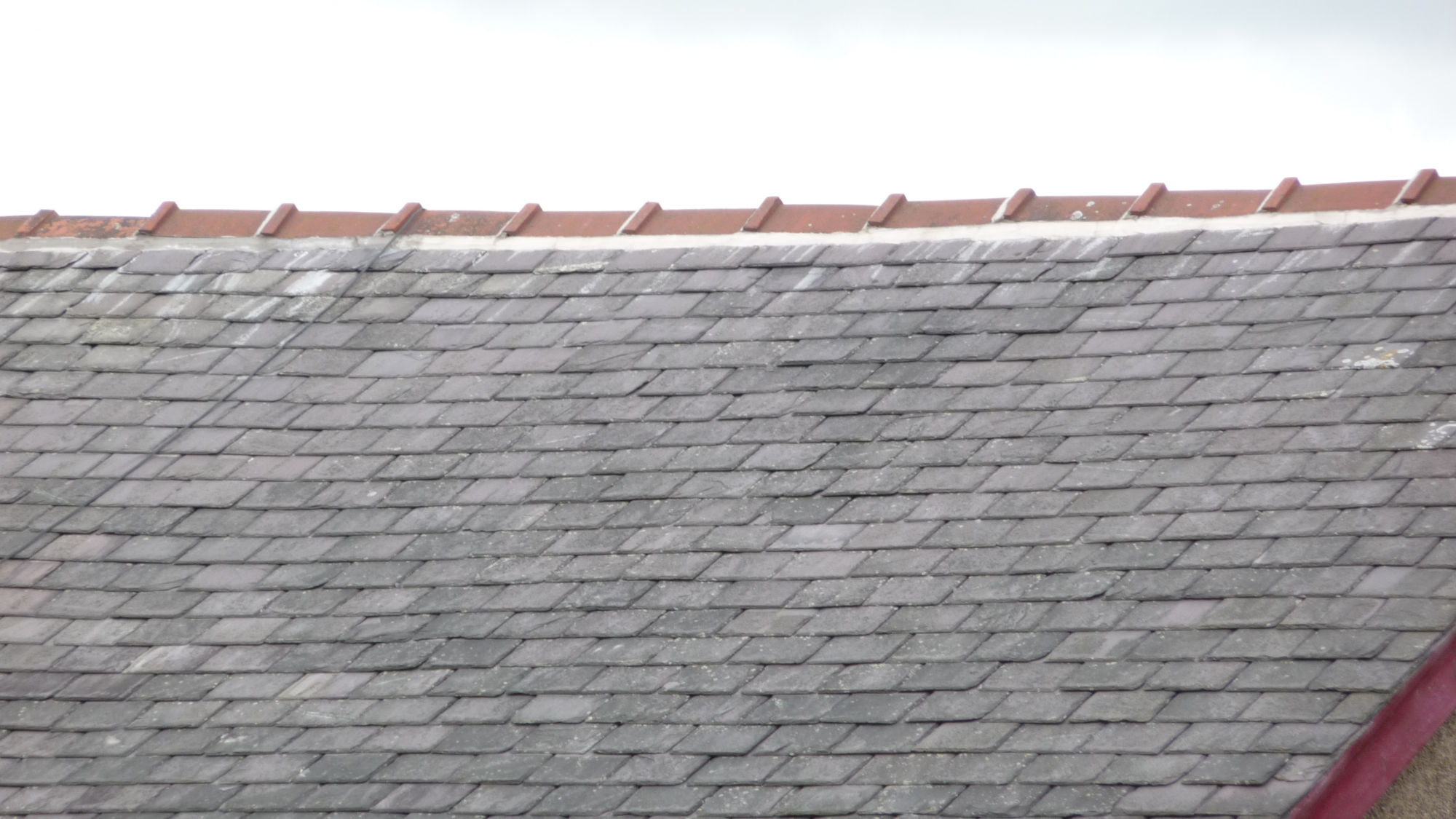Resetting ridge tiles on an end-of-terrace in Colne