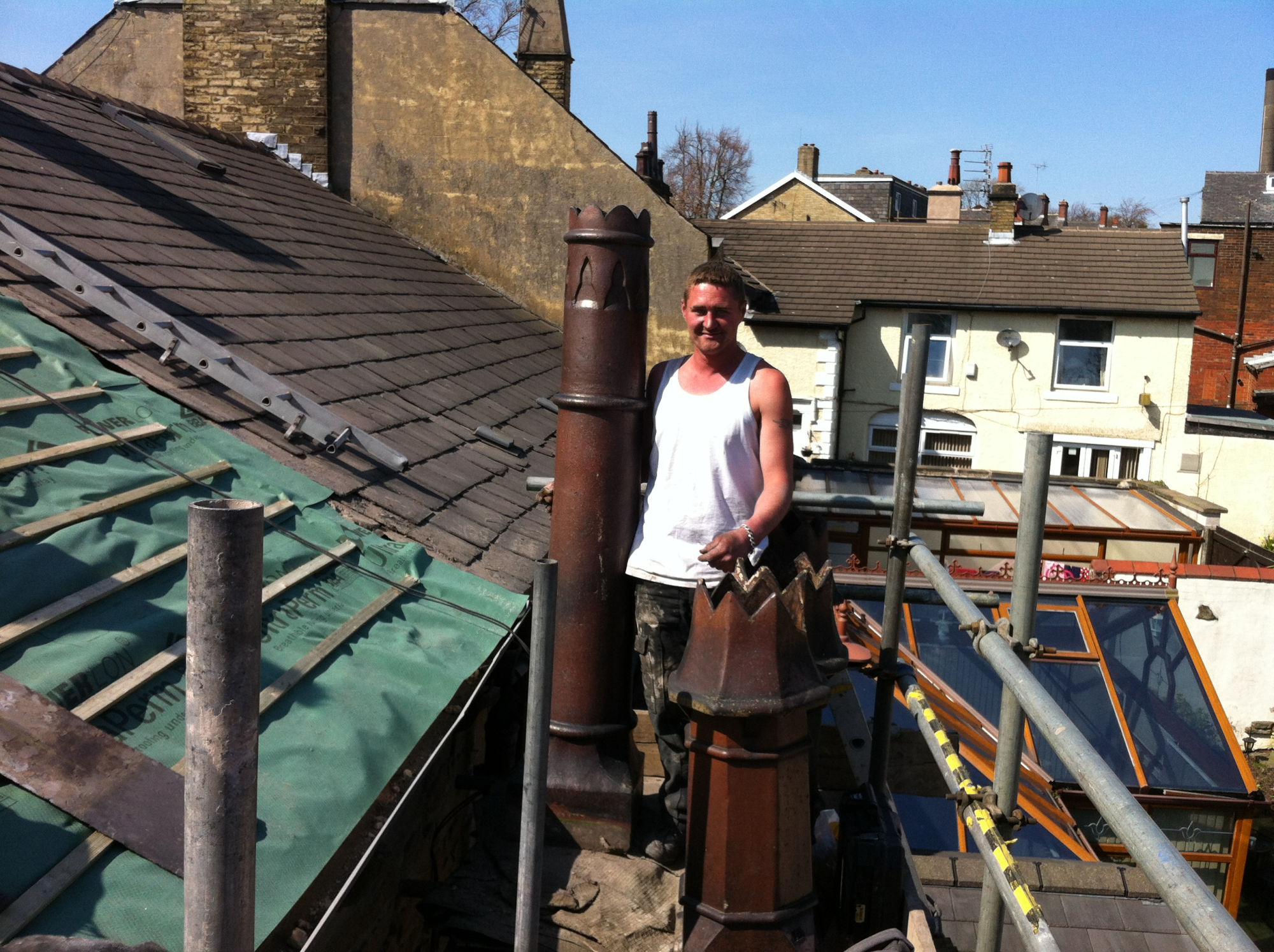 Slate re-roofing among the chimney pots